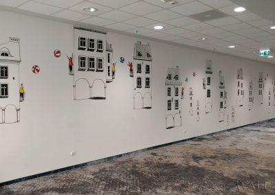 namalowana grafika w korytarzu - latające kamienice - Novotel Poznań